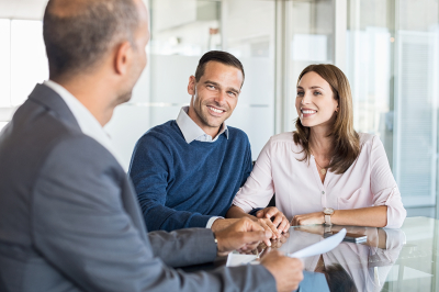 mature financial advisor showing report to young